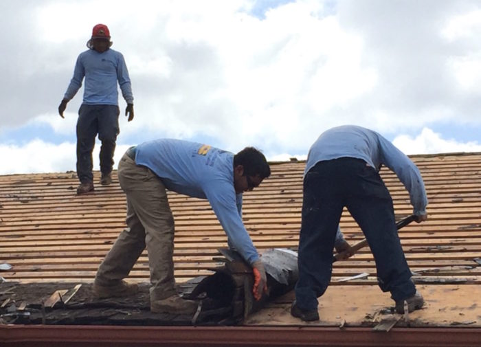 Workers rolling up the old shake roof.
